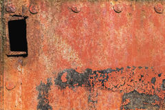 Old Riveted Metal Plate Surface With Decomposed Cracked Flaky Red Anti-corrosive Paint And Patches Of Tar And Rust. Old, scrapped, badly corroded rusty metal Stock Photography