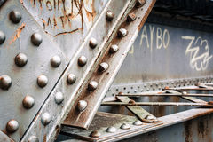 Riveted Steel Surface. Close-up of riveted metal structure with graffiti and rust Royalty Free Stock Photo