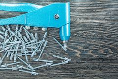 Riveting pliers heap of screws on wooden board Royalty Free Stock Photo