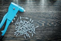 Riveting pliers pile of screws on wooden board Stock Images