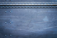 Rivets on metal. Rivets on scratched metal with seams stock image