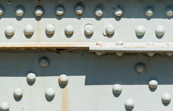 Rivets on painted steel surface with rust stains. Stock Photo