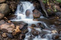 Rivière avec la petite cascade et beaucoup de roches image libre de droits