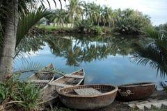 Rivière avec les bateaux en bambou traditionnels au Vietnam Photo stock