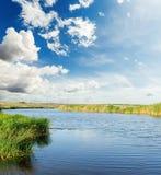 Rivière avec les côtés verts sous le ciel bleu avec des nuages Photographie stock libre de droits