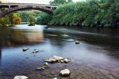Rivière avec les pierres et le brige Image stock