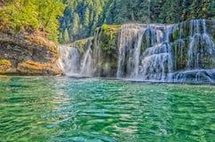 Rivière cascadant au-dessus de la roche dans une piscine de vert vert Photos libres de droits