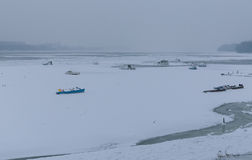 Rivière congelée Danube en glace, bateaux de pêche Photographie stock libre de droits