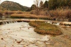 Rivière de Cabriel sur son chemin par le village de Rio de del de maisons, Albacete, Espagne Image stock