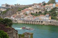 Rivière de Douro avec le bateau de touristes et la Porto Porto en centre ville vu des ruines romantiques d'église Photos stock