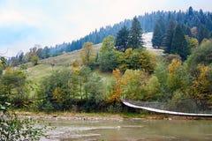 Rivière de montagne avec le pont accrochant par temps pluvieux brumeux Photos stock