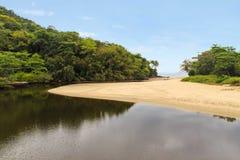 Rivière de Sahy coulant dans l'océan Photographie stock