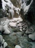 Rivière entre les montagnes rocheuses avec une neige et les glaçons Photographie stock