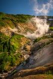 Rivière et cascades entre les caractéristiques thermiques du volcan de Mutnovsky Photos stock