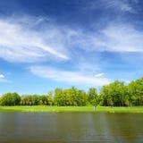 Rivière et la pelouse verte, homme montant une bicyclette Photos libres de droits