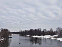 Rivière et neige d'hiver contre un ciel bleu avec des nuages image libre de droits