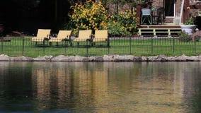 Rivière paisible passant les yards résidentiels avec des chaises banque de vidéos