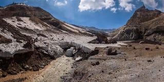 Rivière passant sous la couche glaciale épaisse du glacier à l'intérieur du cratère de volcan de Mutnovsky Photos stock