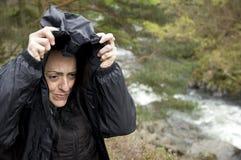 Rivière proche froide de randonneur féminin abritant de la pluie Image stock