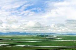 Rivière sinueuse dans la prairie verte avec le ciel bleu Images stock