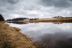Rivière tôt de ressort et ciel nuageux Photographie stock libre de droits