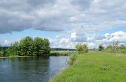 Rivière, terre avec des arbres et ciel nuageux Photographie stock