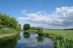 Rivière, terre avec des arbres et ciel nuageux Images libres de droits