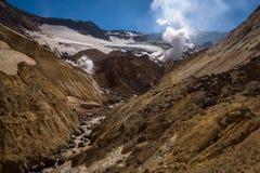 Rivière traversant le canyon avec des fumerolles à l'intérieur de cratère de volcan de Mutnovsky Photos stock