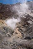 Rivière traversant le canyon avec des fumerolles à l'intérieur de cratère de volcan de Mutnovsky Photographie stock libre de droits