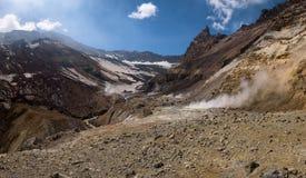 Rivière traversant le canyon avec des fumerolles à l'intérieur de cratère de volcan de Mutnovsky Photo libre de droits
