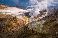 Rivière traversant le canyon avec des fumerolles à l'intérieur de cratère de volcan de Mutnovsky Images stock