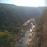 Rivière traversant les collines image libre de droits