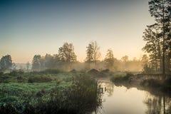 Rivier in de mist, vlak vóór zonsopgang Een warme gloed in de wolken van de eerste stralen van de zon stock afbeeldingen