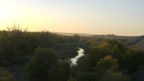 rivier in de vallei tegen de achtergrond van de zon van de zonsondergangherfst stock afbeeldingen