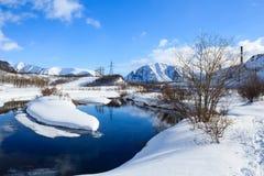 Rivier en behandeld met sneeuwbanken in Russische polaire stad royalty-vrije stock afbeelding