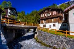 Rivier en chalet in Zwitsers dorp in Alpen, Leukerbad, Leuk, Visp stock afbeelding