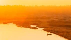 Rivier en het roeien vissersboot bij mooie zonsopgang Royalty-vrije Stock Afbeeldingen