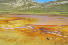 Rivier met het oranje water van de metaalkleur Stock Afbeeldingen