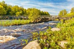 Rivier met oude brug in Zweden royalty-vrije stock afbeeldingen