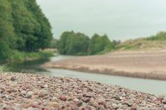 Rivier met rotsachtige die kustlijn door bos wordt omringd Stock Foto