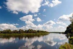 Rivier met wolkenbezinning Stock Afbeeldingen