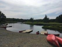 Rivier in ochtendzonneschijn met kano's en boten stock fotografie