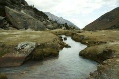 Rivier op de weide in berg stock afbeeldingen