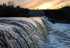 Rivier op zonsondergangachtergrond Stock Foto