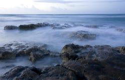 The Riviera Maya coast. Waves hitting rocks along the Riviera Maya coast in Mexico at dawn royalty free stock photo