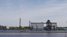 Rivieraak het hoy gaan langs de rivier Daugava met een escavator aan boord - Zonnig weer met haven op de achtergrond stock videobeelden