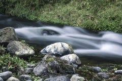 Rivierstroom met rotsenlandschap met een grasachtergrond royalty-vrije stock foto