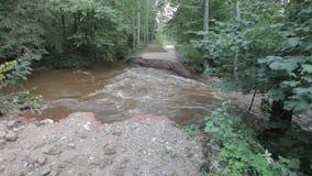 Riviervloed gebroken weg na zware regenval stock video