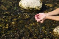 Rivierwater in mijn handen Stock Foto