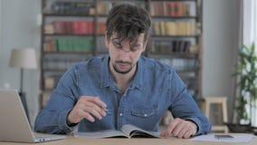 Rivista della lettura del giovane, libro in ufficio casuale stock footage
